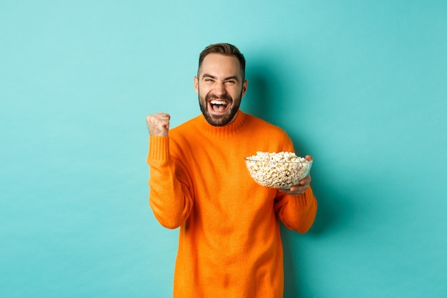Cheerful handsome man in orange sweater, saying yes, cheering and rejoicing, eating popcorn and watching sports, making fist pump satisfied, standing over blue background.