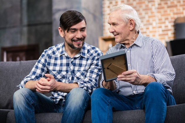 Cheerful handsome man sitting on the sofa with his father while recollecting the past