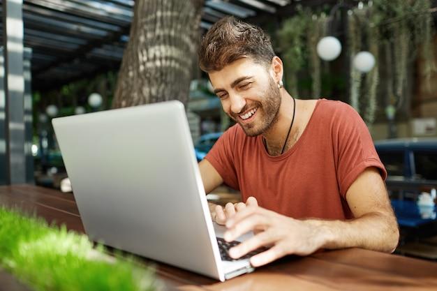 Веселый красавец разговаривает с другом в интернете, печатает на ноутбуке и улыбается счастливым