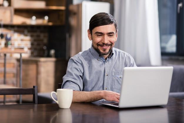 Веселый красавец, используя свой ноутбук, наслаждаясь удаленной работой
