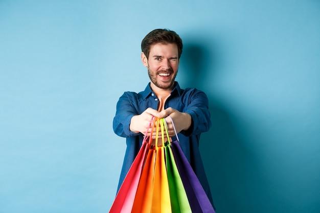 青い背景の上に立って、カラフルな買い物袋で手を伸ばして、ウインクと笑顔の陽気なハンサムな男。