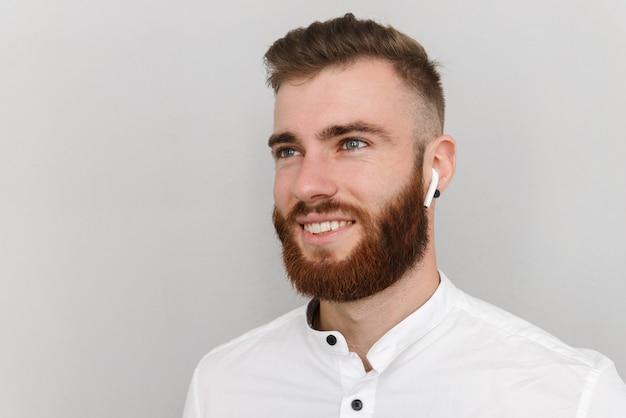 Веселый красавец с бородой улыбается и использует наушники, изолированные на серой стене