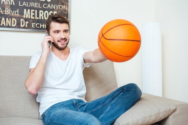 ソファに座って、自宅でバスケットボールのボールで遊ぶスマートフォンを持つ陽気なハンサムな男