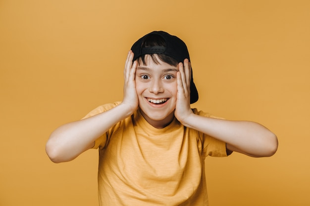 Cheerful handsome young boy dressed in yellow t-shirt and baseball cap putting his palms on his face in surprise, shocked by insane discount.