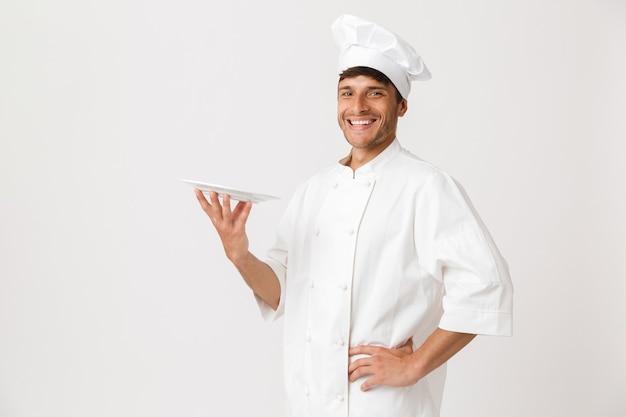 プレートを保持している白い壁に孤立して立っている陽気なハンサムな若いシェフの男。