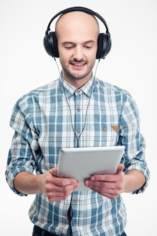 Cheerful handsome young man in checkered shirt listening to music using tablet and earphones over white bacjground