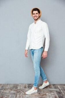 Веселый красивый молодой человек в белой рубашке, джинсах и шляпе улыбается и гуляет