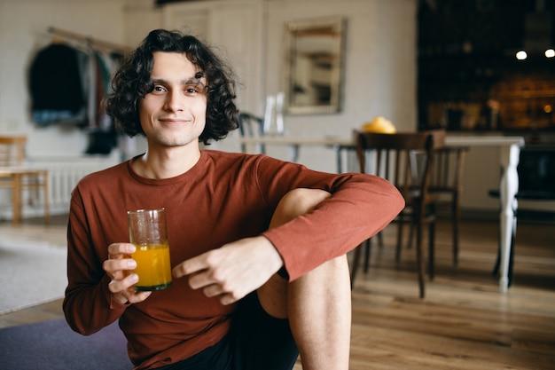 陽気なハンサムな若い男が床に座って、朝食に新鮮なオレンジを持ってジュースを断食し、カメラで幸せそうに笑っている