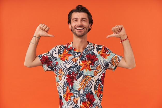 Allegro bel giovane con setole in camicia hawaiana sembra fiducioso e indica se stesso con due pollici