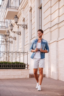 Cheerful handsome young man with photo camera walking in the city
