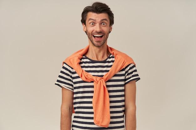 ストライプのtシャツと肩にセーターの無精ひげを持つ陽気なハンサムな若い男は興奮してカメラを見て感じます