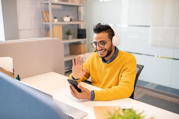 ひげが机に座って、電話でビデオ通話をしながら同僚に手を振って陽気なハンサムな若い中東マネージャー