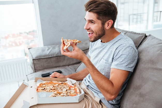 Cheerful hangry young man eating pizza while sitting on sofa and watching tv.