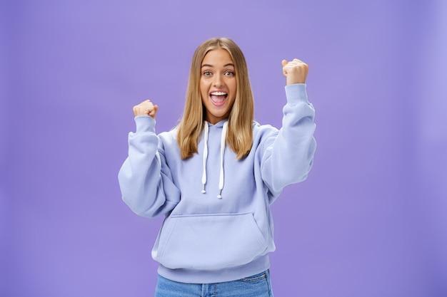Веселая, счастливая и благосклонная молодая девушка со светлыми волосами и загаром в теплом капюшоне поднимает кулаки ...