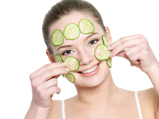 Cheerful happy beautiful girl applying facial mask of cucumber isolated on white