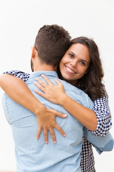 Cheerful happy beautiful woman hugging boyfriend