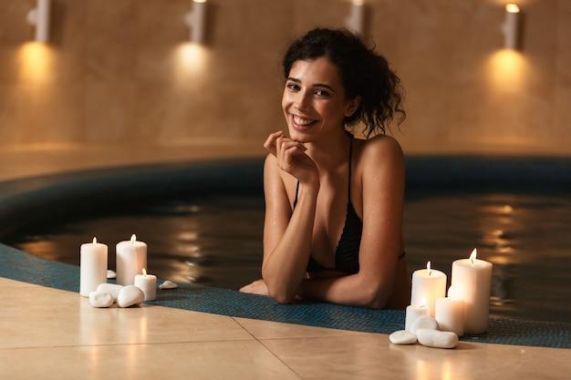 스파에서 밝고 행복 한 아름 다운 여자는 촛불 휴식 거짓말.