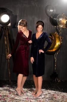 陽気な幸せな美しい若い女性は、パーティーの黒い背景に笑っています。パーティー、休日、クリスマス、誕生日のコンセプト。紙吹雪。紙吹雪、雪、風船の周りで笑っている黒いドレスのモデル