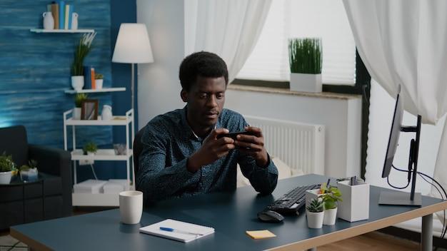 Веселый счастливый темнокожий мужчина играет в видеоигры на своем телефоне