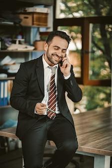 Веселый счастливый бизнесмен разговаривает с мобильным телефоном, сидя на столе