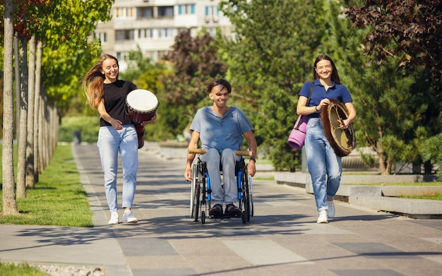 Cheerful. happy caucasian handicapped man on a wheelchair spending time with friends playing live instrumental music outdoors. concept of social life, friendship, possibilities, inclusion, diversity.