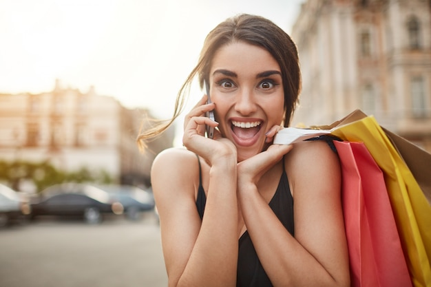 Cheerful happy caucasian woman with dark hair in black dress being happy after boyfriend said they going onsea for vocation. woman talking on phone, holding shopping bags in hands, looking