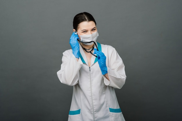 Cheerful happy doctor with crossed hands on grey background