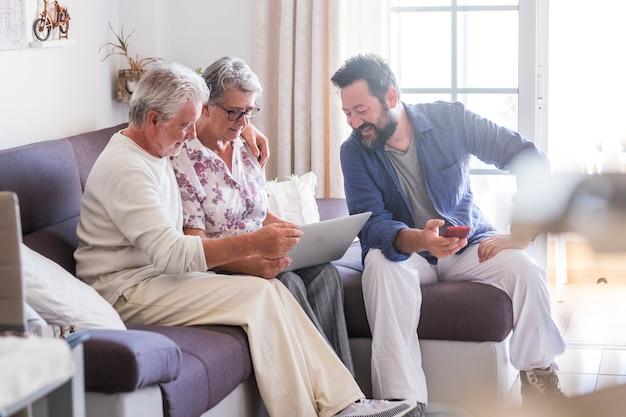 Веселая счастливая семья дома, сидя на диване с современными технологическими устройствами