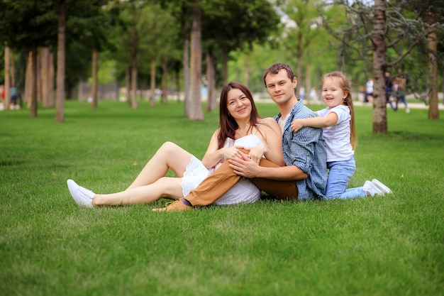 Cheerful happy family embracing and looking at camera while resting on green grass on sunny day in park