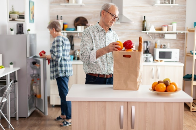 쾌활한 행복한 가족의 건강한 생활 방식은 신선한 과일과 식료품을 냉장고에 넣습니다. 나이든 남편과 아내가 슈퍼마켓에서 도착한 후 식료품 종이 봉지에서 야채를 꺼냅니다.