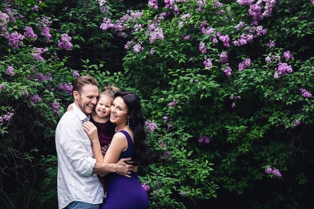 Веселая счастливая семья обнимается возле цветущих кустов сирени.