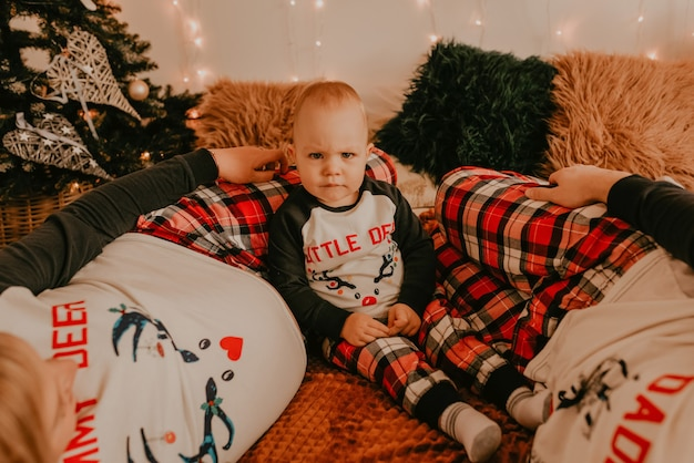 子供と一緒にパジャマを着た陽気な幸せな家族は、寝室のベッドに横たわっています。新年の家族の服は衣装に見えます。バレンタインデーのお祝いの贈り物