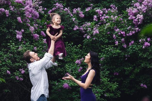 Веселая счастливая семья возле кустов сирени цветения. папа подбрасывает дочку.