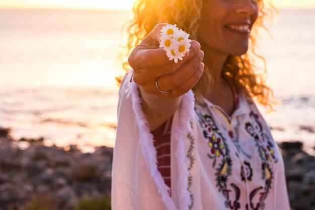 ヒッピーファッションの服を着た陽気な幸せな無料の白人の中年女性は、美しいデイジーの花を取ります-花と太陽のバックライトに焦点を当てます