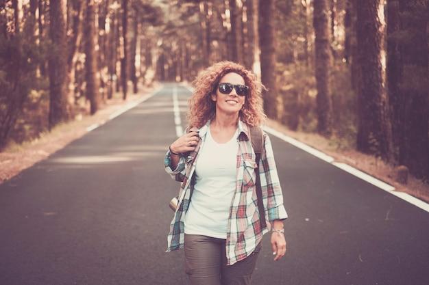 森や木々のある長い道の真ん中を歩く陽気で幸せな自由な女性旅行者