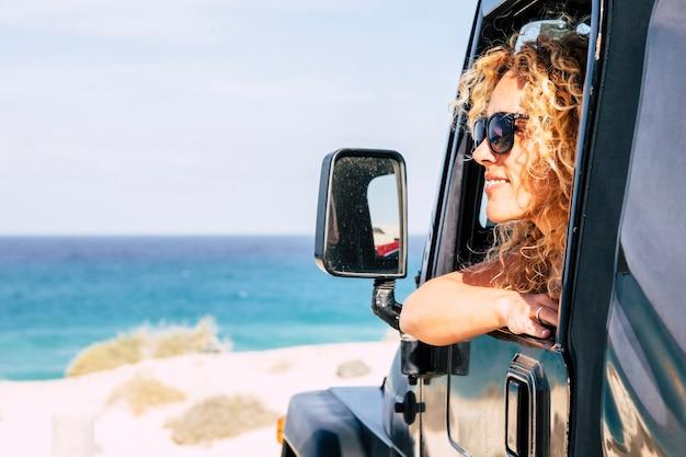 陽気な幸せな自由nrautiful白人の若い女性は青い空と海の背景を持つビーチで車の外を見る-旅行と夏のライフスタイルの人々の概念