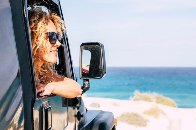 陽気な幸せな自由nrautiful白人の若い女性は青い空と海のシーンとビーチで車の外を見る