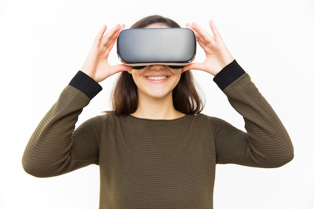 Cheerful happy gamer in vr headset touching device
