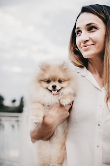 Cheerful and happy girl holds and hugs pomeranian spitz dog