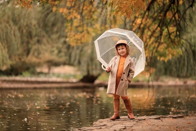 Веселая счастливая девушка с прозрачным зонтиком на прогулке осенью у озера