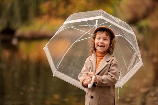 湖のほとりの秋の散歩に透明な傘を持つ陽気な幸せな女の子