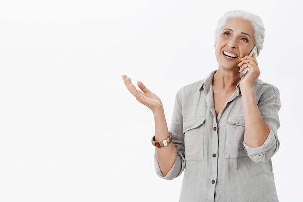 Веселая счастливая бабушка разговаривает по мобильному телефону и улыбается