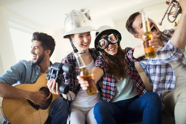 Cheerful happy group of friends having fun while playing instruments and drinking