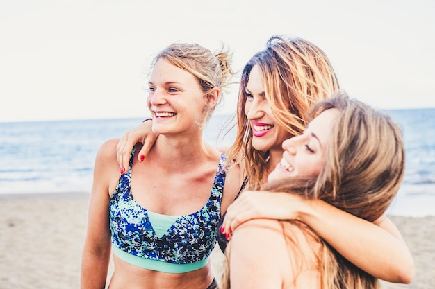 スポーツウェアのビーチで3人の若い白人の友人の女性の陽気な幸せなグループは友情を楽しんで一緒にたくさん笑います-アクティブなミレニアル世代のための幸せと喜び