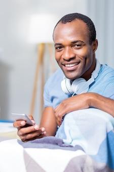 Веселый счастливый красивый мужчина улыбается и в наушниках, используя свой смартфон