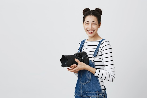 Cheerful happy hipster girl taking photos, laughing and using camera, photographing
