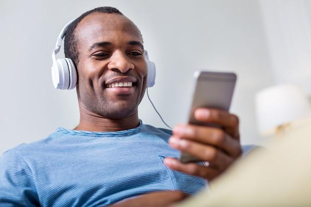 Веселый счастливый радостный мужчина улыбается и смотрит на экран смартфона, слушая свою любимую песню