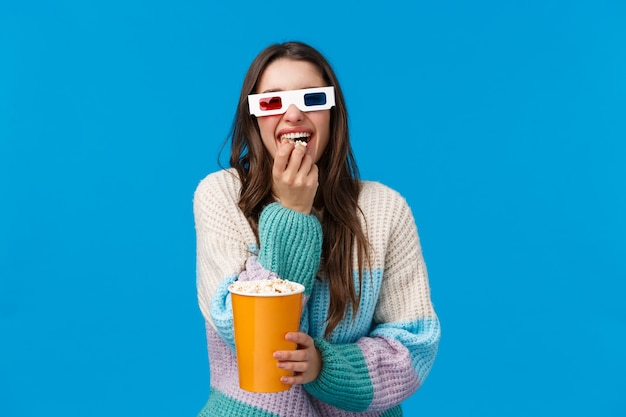 Cheerful and happy, laughing brunette caucasian girl enjoying funny movie, wearing 3d glasses, chuckling and munching popcorn, holding box, standing in winter sweater, cinema offer student dicsount