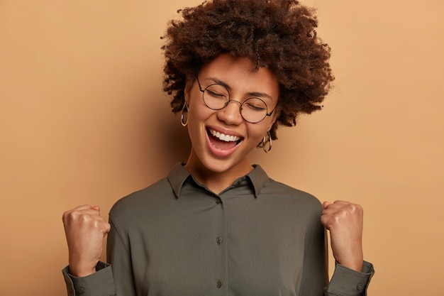 Cheerful happy lucky businesswoman achieves goal, celebrates victory, signing profitable agreement with partner, wears optical glasses and shirt, isolated on brown wall. student passed test