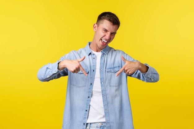 Allegro studente maschio felice in abiti casual consiglia di iscriversi a corsi di lingua, puntando il dito verso il basso al banner, sorridendo eccitato, invitando all'evento, promuovendo una buona offerta, sfondo giallo